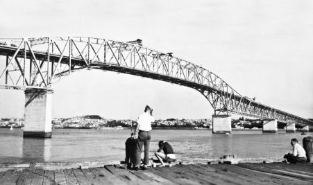 "Fishing from Northcote Wharf with a view of the new (but not complete) Auckland Harbour Bridge. Opened May 30, 1959. ""Clip-on"" lanes added 1969."