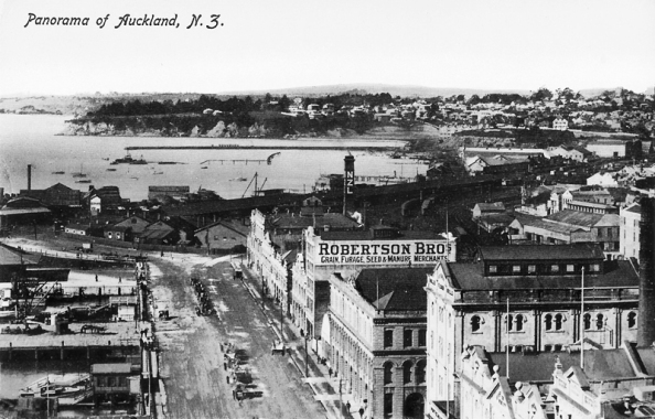 Looking east from the Ferry Buildings down Quay Street East and over Mechanics Bay, with St Barnabas Point (being demolished, right distance), St Georges Bay and Parnell (right), Campbells Point (centre distance), with Quay Street Jetties (left foreground), and premises of Lichenstein Arnoldson and Company, Northern Roller Milling Company, New Zealand Shipping Company, Robertson Brothers, Northern Steamship Company, New Zealand Laundry Company and other premises along Quay Street East (right to centre), premises in Customs Street (right), Railway Station (right, middle distance), with yard of D Goldie, timber merchant (left, middle distance)