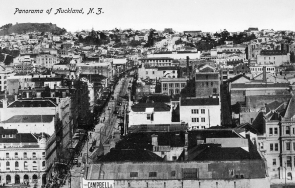 Looking south from Ferry Building over city to Mount Eden (left background), showing buildings in Queen Street (left of centre), premises of Thames Hotel, Campbell and Ehrenfried Company Limited and Customs Buildings (left to right, foreground)